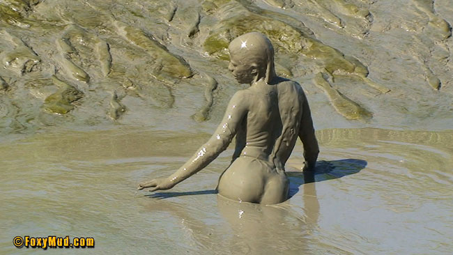 Naked girl in deep mud